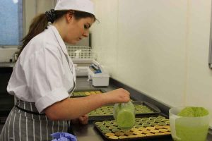 Apprentice Rosie Cockton preparing goats cheese and spinach tarts at Truro College.